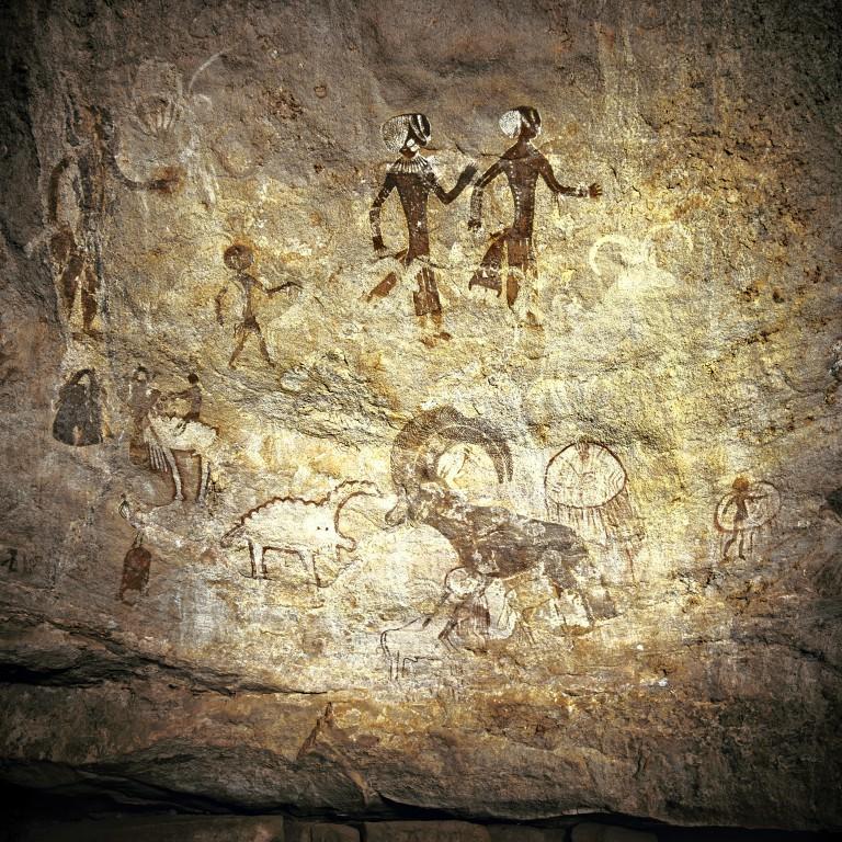 Un mouflon à manchettes et deux femmes élégantes dominent un univers fait de personnges et d'animaux mystérieux (Site de Tam Zoumaïtak, Tassili n'Ajjer, Algérie).